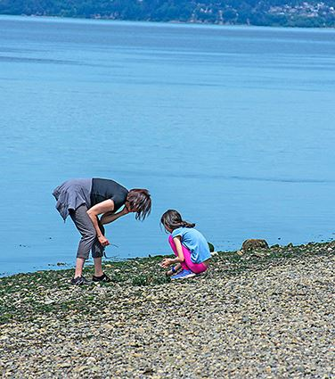 Mother and child picking up rocks on shore